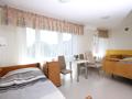 : pokój dobrze doświetlony światłem słonecznym, dwuosobowy z dwoma pojedynczymi łóżkami. widok z okien na pobliskie osiedle. pod oknem stoliczek i dwa krzesła. pokój w pastelowych ciepłych barwach z dodatkami brązu, beżu i żółcieni.