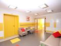 kącik wypoczynkowy na drugim piętrze domu. dwa duże wygodne fotele i stoliczek kawowy stoją pod jasną ścianą z żółtymi pasami. nad kącikiem przepiękny obraz z czerwonymi makami. po przeciwnej stronie duża wygodna kanapa z żółtymi i czerwonymi poduszeczkami.
