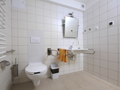 łazienka w jasnobeżowych kafelkach z nisko zawieszoną umywalką oraz uchwytami dla osób niepełnosprawnych. nad umywalką duże lustro z możliwością regulacji kąta nachylenia. po lewej stronie pomieszczenia  kompakt wc w białym kolorze oraz uchwyty wspomagające korzystanie z toalety. na ścianie system alarmowo-przyzywowy.