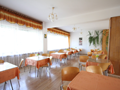 jadalnia znajdująca się na parterze domu mieszcząca stoliki z krzesłami. stoły przykryte pomarańczowymi serwetami pasującymi do lambrekinów w oknach. na ścianie kolorowe obrazy z motywami kuchennymi oraz zielone zwisające paprotki.