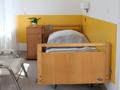 łóżko rehabilitacyjne z możliwością regulacji nachylenia poszczególnych segmentów. kółka z indywidualnym systemem blokowania oraz barierki z możliwością podniesienia i opuszczenia w razie potrzeby. nad łóżkiem lampka nocna i system alarmowo- przyzywowy. po lewej stronie szafka przyłóżkowa z rozkładanym stolikiem.