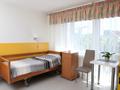 widok na pokój z drzwi łazienki. łóżko, szafka przyłóżkowa oraz stolik i dwa krzesła. w każdym pokoju wyjście na balkon.