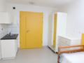 ten sam pokój. widok na aneks kuchenny znajdujący się przy drzwiach wyjściowych. widoczny jest również domofon po lewej stronie drzwi. po prawej stronie pojemna szafa z lustrem oraz niewielka komoda.