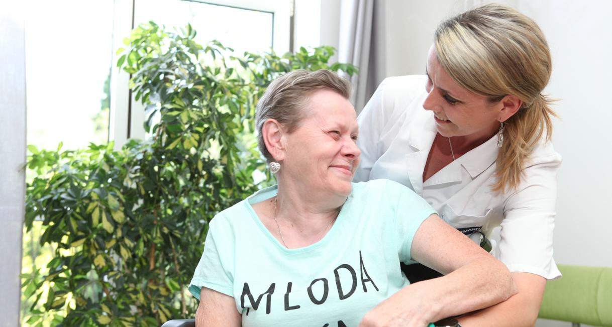 miła opiekunka obejmuje kobietę siedzącą na wózku inwalidzkim. rozpromienione twarze kobiet ukazują szczęście wynikające z wspólnego uścisku.