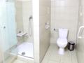 łazienka z widocznym po lewo z otwartym prysznicem. niski brodzik, siedzisko i nisko umieszczona słuchawka prysznicowa. po prawej stronie kompakt  wc w białym kolorze obok uchwyt dla osób niepełnosprawnych i system alarmowo-przyzywowy. W pomieszczeniu jasne kafelki i srebrne dodatki takie jak uchwyt na papier toaletowy i niski kosz na śmieci.