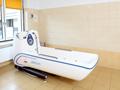 pokój kąpielowy. na środku stoi duża wanna z udogodnieniami dla osób niepełnosprawnych i hydromasażem. pomieszczenie jest czyste i zadbane. na ścianie zamontowany jest system alarmowo-przyzywowy.