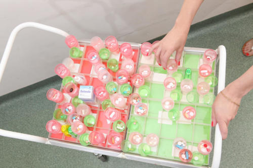 zdjęcie wózek czerwono- zielony z przegródkami i kieliszkami wypełnionymi lekami dla mieszkańców domu.
