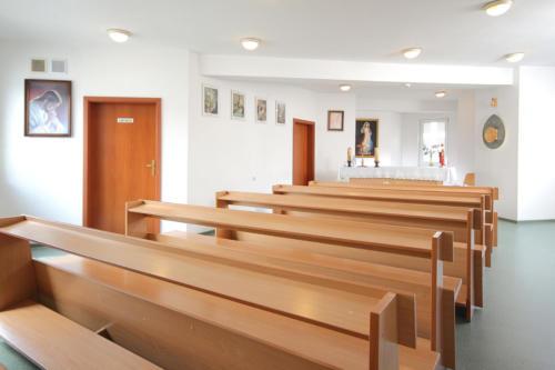 zdjęcie widok kaplicy z dalszej perspektywy. ołtarz, zakrystia, ławki i tabernakulum.