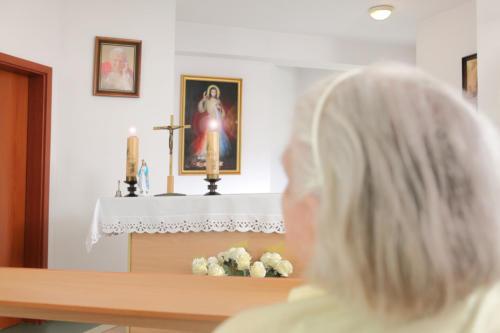 zdjęcie mieszkanka domu zapatrzona w ołtarz i obraz Jezusa Miłosiernego.